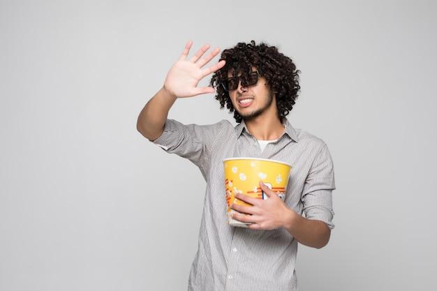 Młody Przystojny Mężczyzna Nosić Okulary 3d Z Kręconymi Włosami, Trzymając Miskę Popcorns Na Pojedyncze Białe ściany Darmowe Zdjęcia