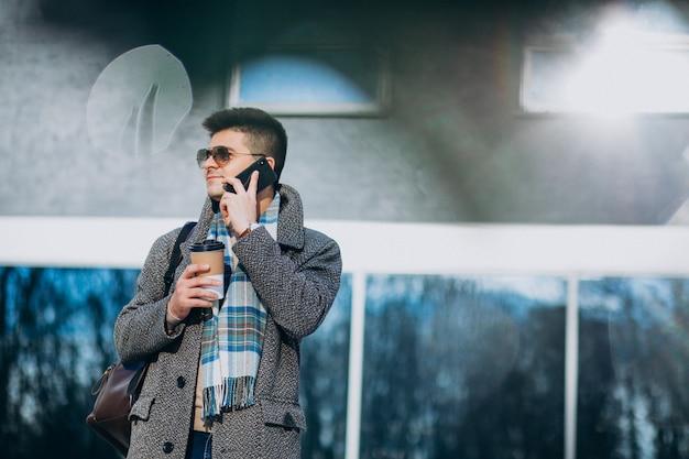 Młody Przystojny Mężczyzna Pije Kawę Na Zewnątrz I Używa Telefon Darmowe Zdjęcia