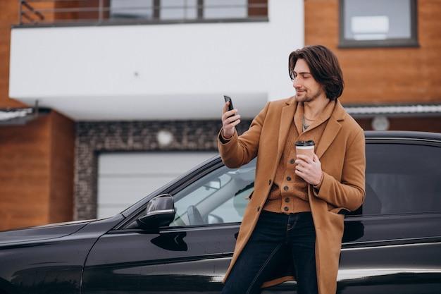 Młody Przystojny Mężczyzna Rozmawia Przez Telefon Przez Samochód Darmowe Zdjęcia
