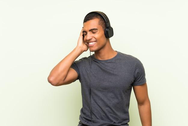 Młody przystojny mężczyzna słuchania muzyki z telefonu komórkowego Premium Zdjęcia
