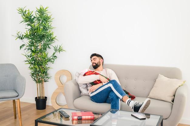 Młody przystojny mężczyzna śpi na kanapie z dzieckiem w ręku w domu Darmowe Zdjęcia