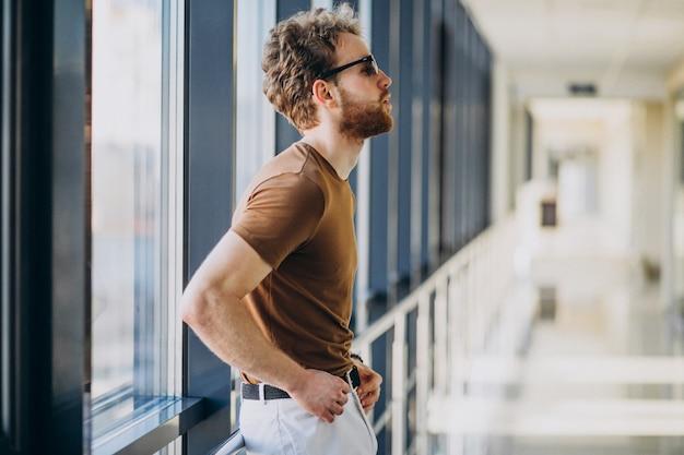 Młody Przystojny Mężczyzna Stojący Przy Oknie Na Lotnisku Darmowe Zdjęcia