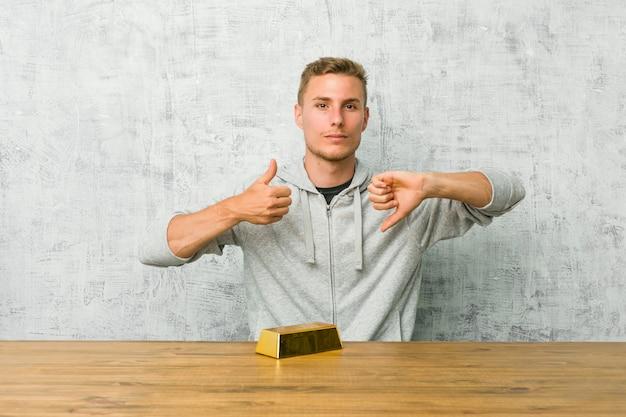 Młody przystojny mężczyzna trzyma złotą sztabkę na stole pokazującym kciuk w górę i kciuk w dół, trudny wybór Premium Zdjęcia