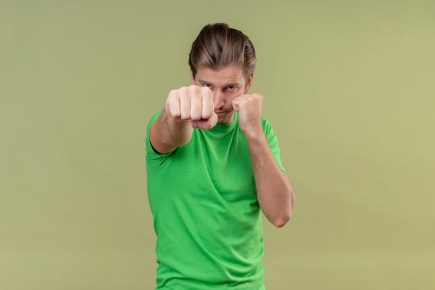 Młody Przystojny Mężczyzna Ubrany W Zieloną Koszulkę Pozuje Jak Bokser Z Zaciśniętą Pięścią Stojący Nad Zieloną ścianą Darmowe Zdjęcia