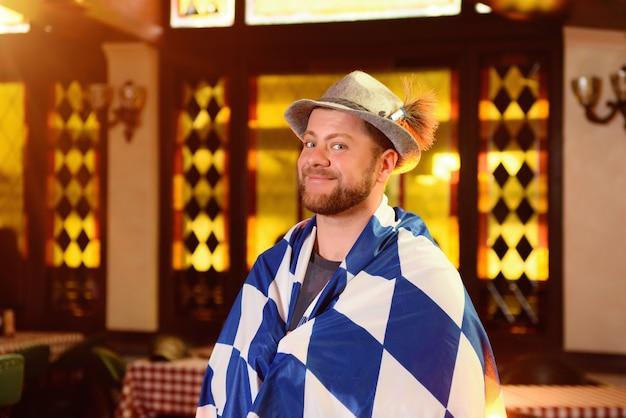Młody Przystojny Mężczyzna W Kapeluszu I Brodą Pod Flagą Oktoberfest Pokazuje Kciuk Up Premium Zdjęcia