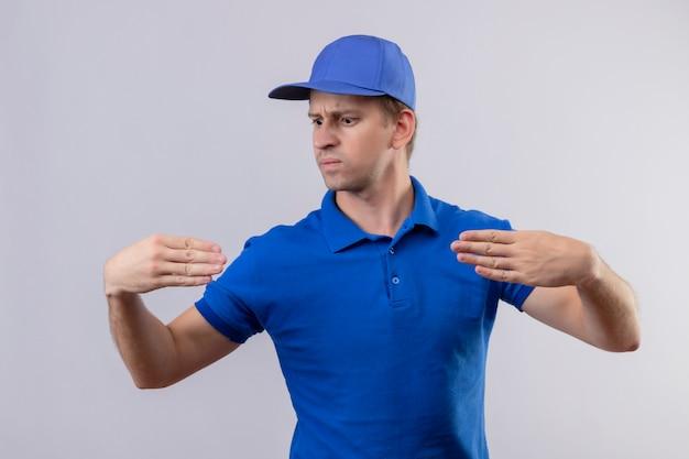 Młody Przystojny Mężczyzna W Niebieskim Mundurze I Czapce, Gestykulując Z Koncepcją Języka Ciała Rąk Stojących Na Białej ścianie Darmowe Zdjęcia