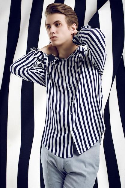 Młody przystojny mężczyzna w pasiastej koszula pozuje na czarny i biały Premium Zdjęcia