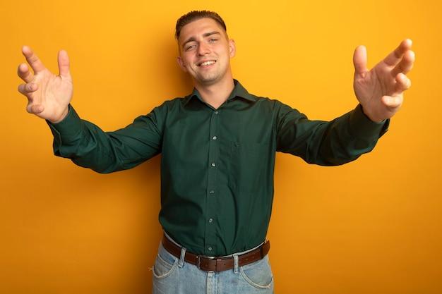 Młody Przystojny Mężczyzna W Zielonej Koszuli Uśmiechnięty Przyjazny Czyniąc Powitalny Gest Szeroko Otwierając Ręce Darmowe Zdjęcia