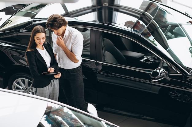 Młody Przystojny Mężczyzna Wybiera Samochód W Samochodowej Sala Wystawowej Darmowe Zdjęcia