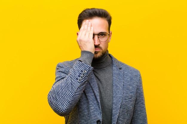 Młody Przystojny Mężczyzna Wyglądający Na Sennego, Znudzonego I Ziewającego, Z Bólem Głowy I Jedną Ręką Zakrywającą Połowę Twarzy Przed Pomarańczą Premium Zdjęcia