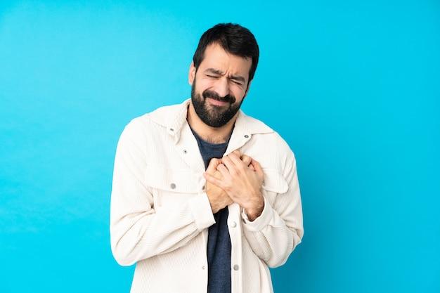 Młody Przystojny Mężczyzna Z Białą Sztruksową Kurtką Nad Odosobnionym Błękitem Premium Zdjęcia