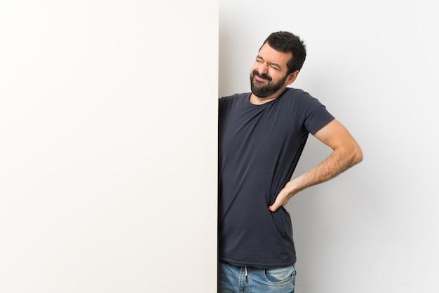 Młody Przystojny Mężczyzna Z Brodą Trzyma Duży Pusty Plakat Premium Zdjęcia