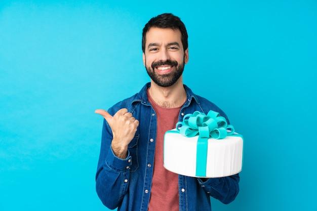 Młody Przystojny Mężczyzna Z Dużym Tortem Nad Odosobnioną Błękit ścianą Z Aprobatami Gestykuluje I Ono Uśmiecha Się Premium Zdjęcia