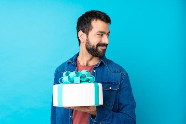 Młody Przystojny Mężczyzna Z Dużym Tortem Nad Odosobnioną Błękit ścianą Z Rękami Krzyżować I Szczęśliwy Premium Zdjęcia