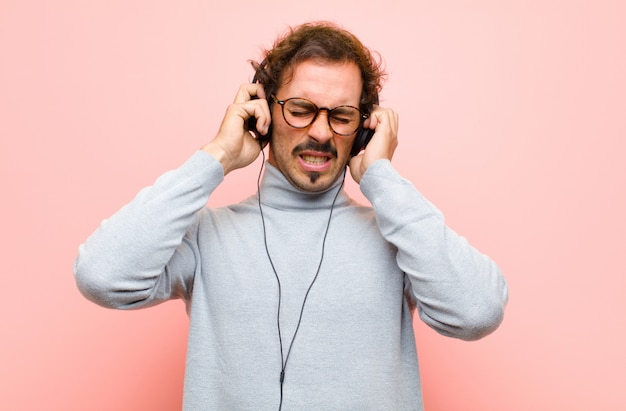 Młody przystojny mężczyzna z hełmofonami przeciw różowej płaskiej ścianie Premium Zdjęcia