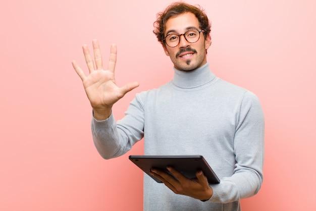 Młody przystojny mężczyzna z pastylką przeciw różowej płaskiej ścianie Premium Zdjęcia