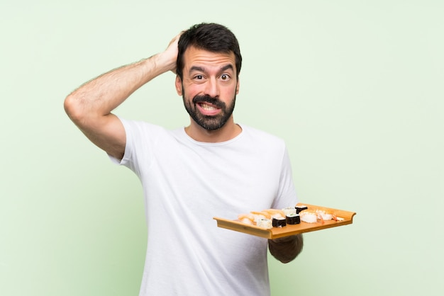 Młody przystojny mężczyzna z sushi na pojedyncze zielone ściany sfrustrowany i bierze ręce na głowę Premium Zdjęcia