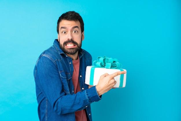 Młody Przystojny Mężczyzna Z Wielkim Ciastem Na Pojedyncze Niebieskie ściany Przestraszony I Wskazując Na Bok Premium Zdjęcia