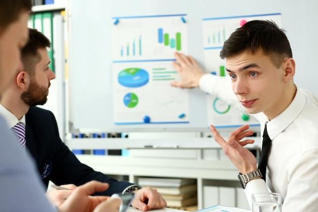 Młody Przystojny Nauczyciel Mężczyzna W Garniturze Z Forum Grupy Roboczej Z Tłem Coachingu Wykresu. Wykładowca Dla Kandydatów Przekwalifikowujących Się W Zakresie Zarządzania Statystyką Finansową, Etykieta Przedsiębiorstwa, Duch Korporacyjny Premium Zdjęcia
