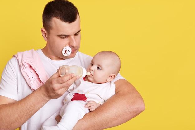 Młody Przystojny Ojciec Karmi Swojego Nowonarodzonego Syna Mlekiem Z Butelki Do Karmienia Premium Zdjęcia
