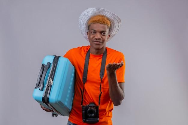 Młody Przystojny Podróżnik Chłopiec W Letnim Kapeluszu Na Sobie Pomarańczową Koszulkę Z Aparatem Trzymając Walizkę Podróżną Darmowe Zdjęcia
