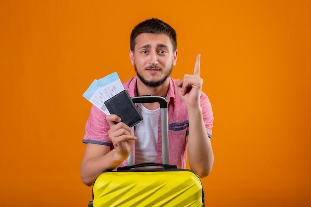 Młody Przystojny Podróżnik Trzymający Bilety Lotnicze Wskazując Palcem W Górę Przypomina Sobie, żeby Nie Zapomnieć O Ważnej Rzeczy Stojącej Z Walizką Na Pomarańczowym Tle Darmowe Zdjęcia