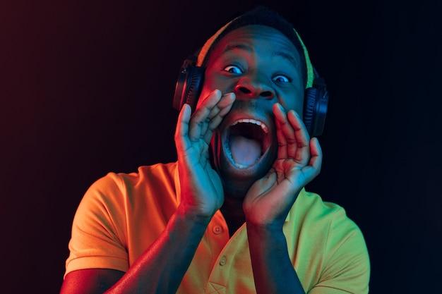 Młody Przystojny Szczęśliwy Hipster Mężczyzna Słuchanie Muzyki W Słuchawkach W Czarnym Studio Z Neonów. Dyskoteka, Klub Nocny, Styl Hip-hopowy, Pozytywne Emocje, Wyraz Twarzy, Koncepcja Tańca Darmowe Zdjęcia