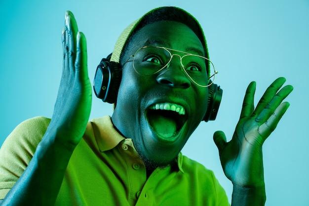 Młody Przystojny Szczęśliwy Zaskoczony Mężczyzna Hipster Słuchanie Muzyki W Słuchawkach W Studio Z Neonów. Darmowe Zdjęcia