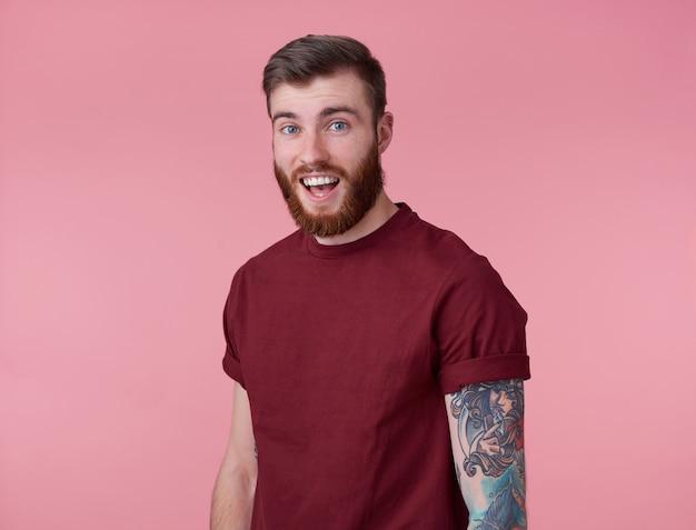 Młody Przystojny Szczęśliwy Zdumiony Czerwony Brodaty Mężczyzna W Pustej Koszulce, Stoi Na Różowym Tle, Wygląda Zaskoczony W Aparat Z Szeroko Otwartymi Ustami I Oczami. Darmowe Zdjęcia