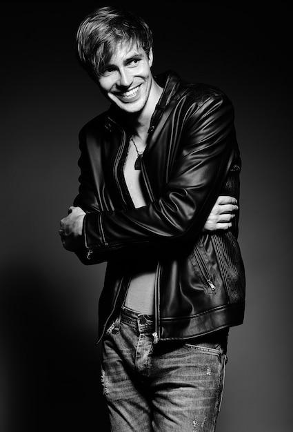Młody Przystojny Umięśniony Sprawny Mężczyzna Model Mężczyzna W Skórzanej Kurtce Pozowanie Studio Pokazano Jego Mięśnie Brzucha Darmowe Zdjęcia
