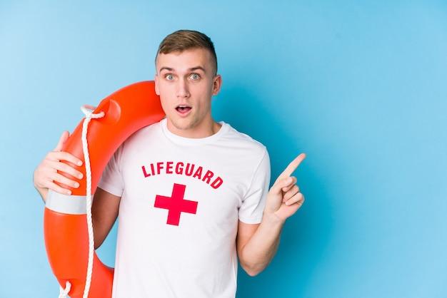 Młody Ratownik Mężczyzna Trzyma Pływak Ratunkowy, Wskazując W Bok Premium Zdjęcia