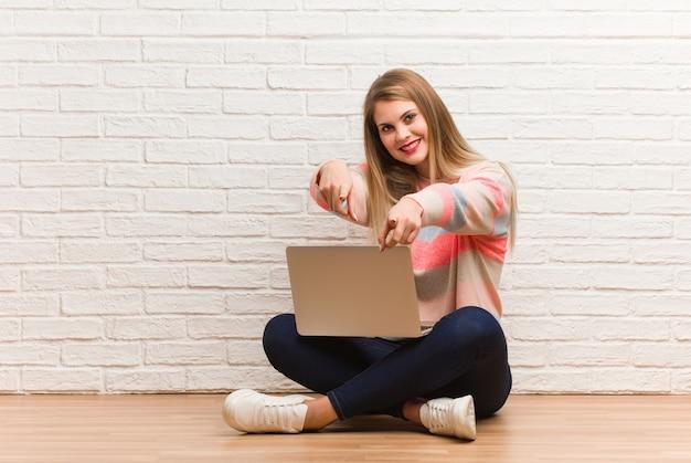 Młody rosyjski studencki kobiety siedzieć rozochocony i uśmiechnięty wskazywać przód Premium Zdjęcia