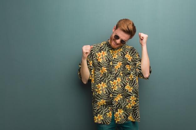 Młody rudzielec mężczyzna jest ubranym egzotycznych lato ubrania tanczy zabawę i ma Premium Zdjęcia