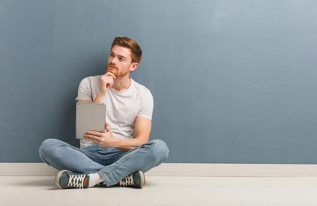 Młody rudzielec studencki mężczyzna siedzi na podłoga wątpić i wprawiać w zakłopotanie. on trzyma tablet. Premium Zdjęcia