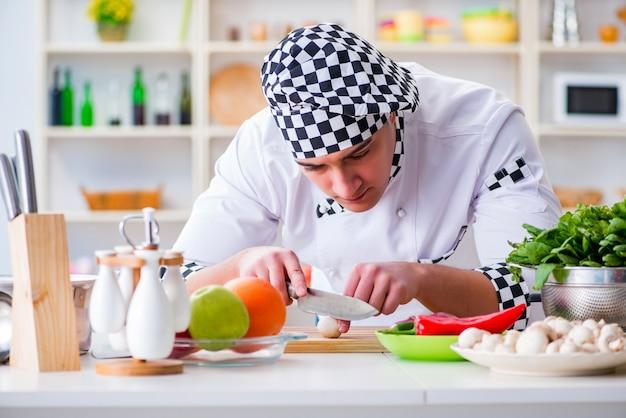 Młody samiec kucharz pracuje w kuchni Premium Zdjęcia