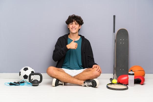 Młody sport człowiek siedzi na podłodze wokół wielu elementów sportowych, podając kciuki gest Premium Zdjęcia