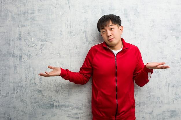 Młody sport fitness chiński wątpi i wzrusza ramionami Premium Zdjęcia
