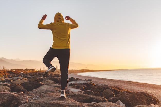 Młody Sporta Mężczyzna W Kapiszonie Robi Skokowi Na Skałach Na Morza I Gór Tle Przy Zmierzchem Premium Zdjęcia
