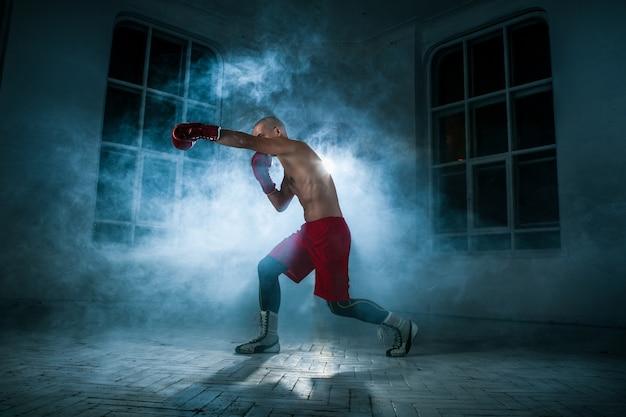 Młody Sportowiec Kickboxingu Na Niebieskim Dymie Darmowe Zdjęcia