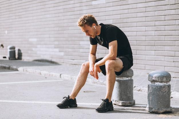 Młody sportowiec zatrzymał się, by usiąść Darmowe Zdjęcia