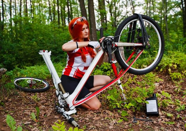 Młody Sportsmenki Rowerzysta Naprawia Jej Rower Mtb W Lesie Premium Zdjęcia