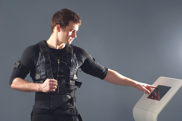 Młody Sprawny Mężczyzna Sportowiec Pchanie Na Ekranie Na Maszynie Ems Regulacji Intensywności. Premium Zdjęcia