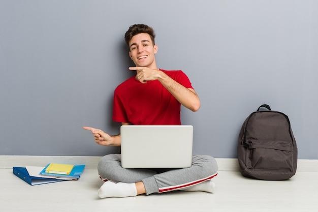 Młody Studencki Mężczyzna Obsiadanie Na Jego Domowej Podłoga Trzyma Laptop Premium Zdjęcia