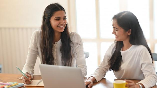 Młody Student Uniwersytetu Prowadzący Lekcję Korzystania Z Komputerowego Laptopa Siedząc Razem Przy Drewnianym Biurku Nad Wygodnym Salonem Premium Zdjęcia