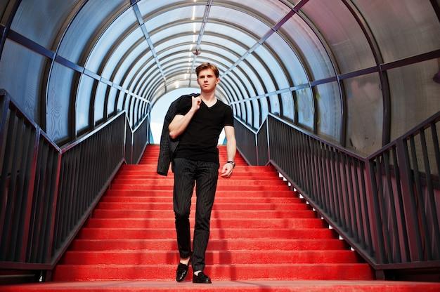 Młody stylowy chłopak macho w czarnej kurtce pozował na zewnątrz ulicy. zadziwiający wzorcowy mężczyzna przy czerwonym schodka tonnelem. Premium Zdjęcia