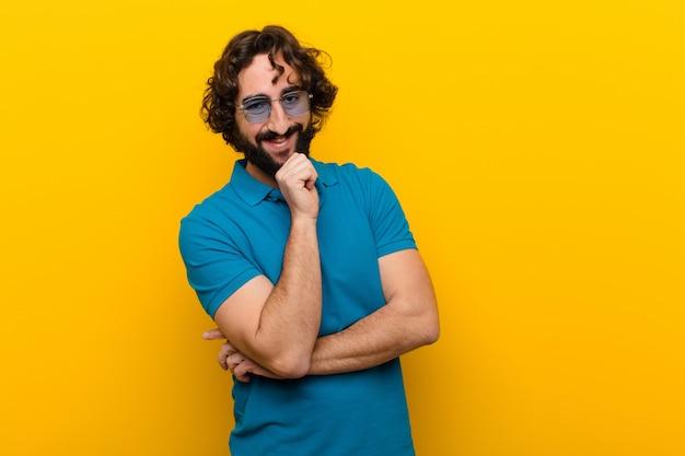 Młody szalony człowiek wyglądający szczęśliwy i uśmiechnięty z ręką na brodzie, zastanawiając się, zadając pytanie, porównując opcje pomarańczowe ściany Premium Zdjęcia