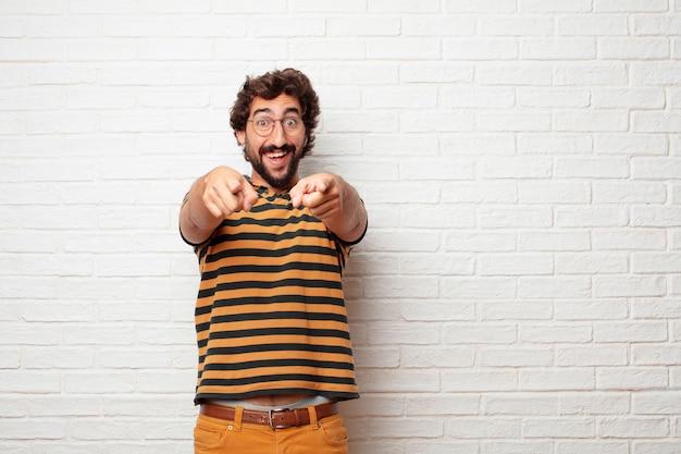 Młody szalony lub niemądry mężczyzna gestykuluje emocje przeciw ściana z cegieł tłu i wyraża Premium Zdjęcia