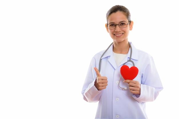 Młody Szczęśliwy Lekarz Kobieta Uśmiecha Się Trzymając Czerwone Serce Premium Zdjęcia