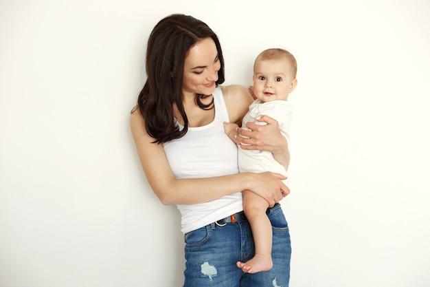 Młody Szczęśliwy Macierzysty Uśmiechnięty Mienie Patrzeje Jej Dziecko Córki Nad Biel ścianą. Darmowe Zdjęcia