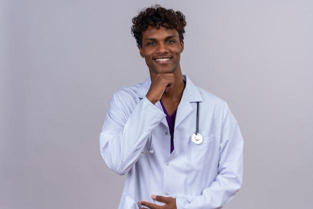 Młody Szczęśliwy Przystojny Ciemnoskóry Lekarz Mężczyzna Z Kręconymi Włosami, Ubrany W Biały Fartuch Ze Stetoskopem, Trzymając Rękę Na Brodzie Darmowe Zdjęcia